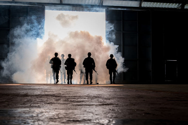 Silhouette army soldiers walking by tear gas walking on floor
