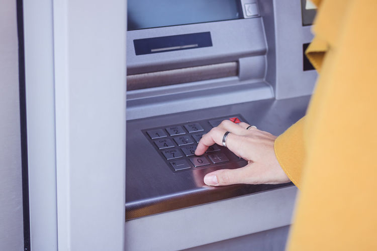 Cropped Hand Of Woman Typing In Atm Machine