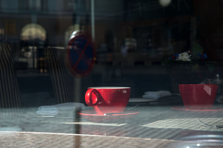 Coffee cups on table in cafe seen through window