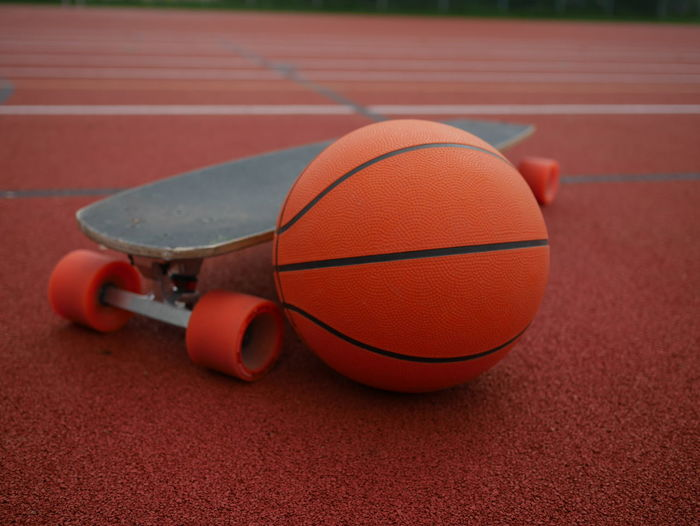 Close-up of basketball and skateboard at park