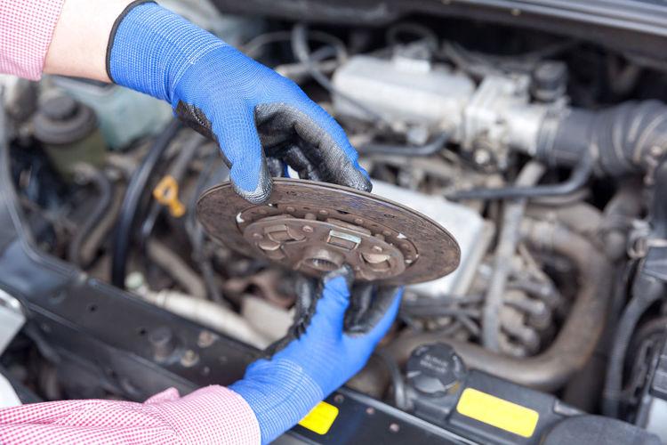 Mechanic Holding Engine Part Against Car