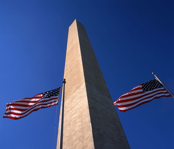 Low angle view of washington monument and american flags against clear blue sky