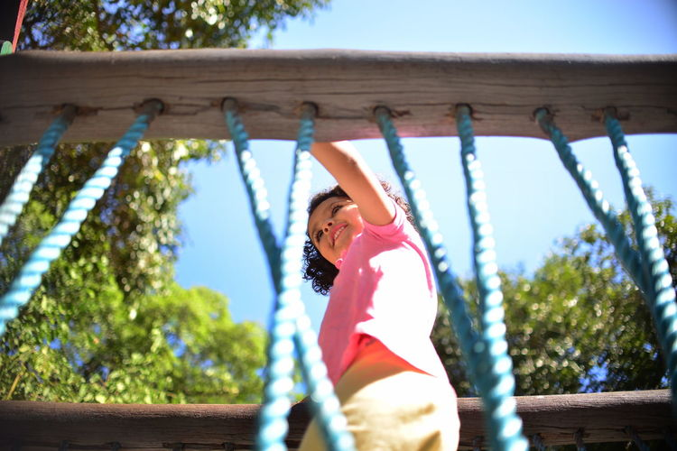 Low Angle View Of Girl At Jungle Gym