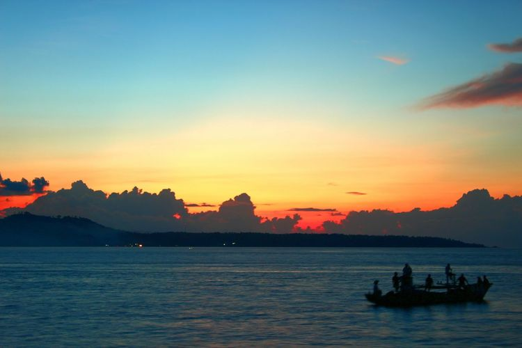 Boats in sea at sunset