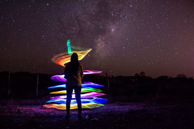 Rear View Of Woman Looking At Colorful Light Painting Against Star Field At Night