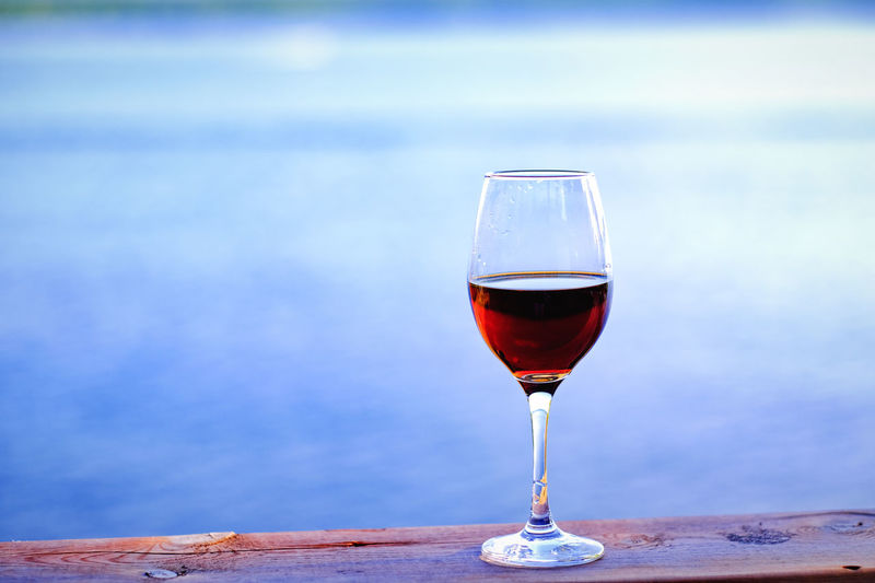 Close-up of wine glass on table against sea