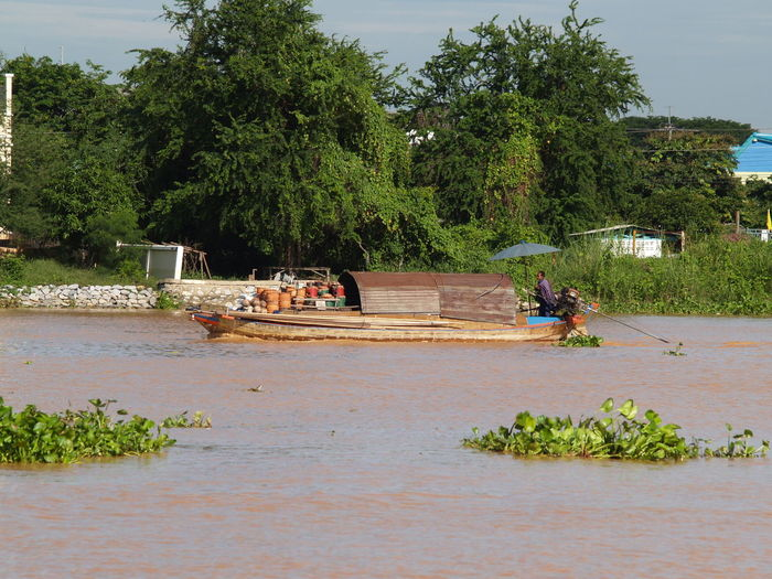 People in boat by river against trees