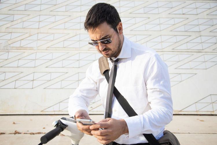 Businessman using smart phone standing outdoors