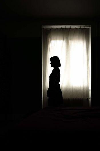 Silhouette woman looking through window