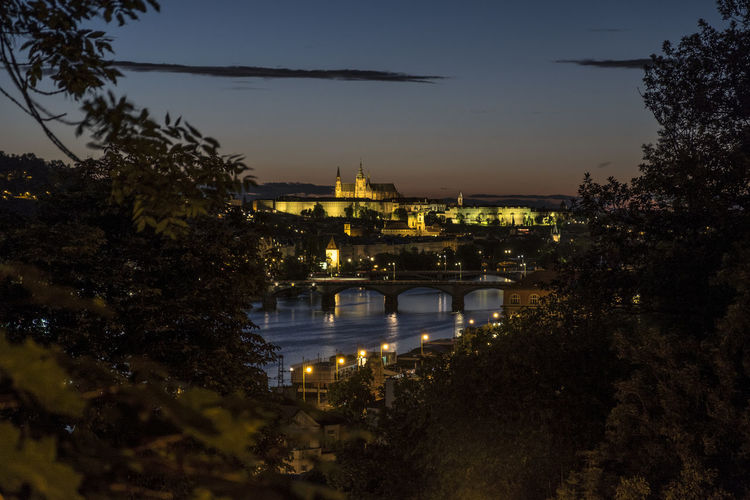 Illuminated bridge over river in city against sky at dusk