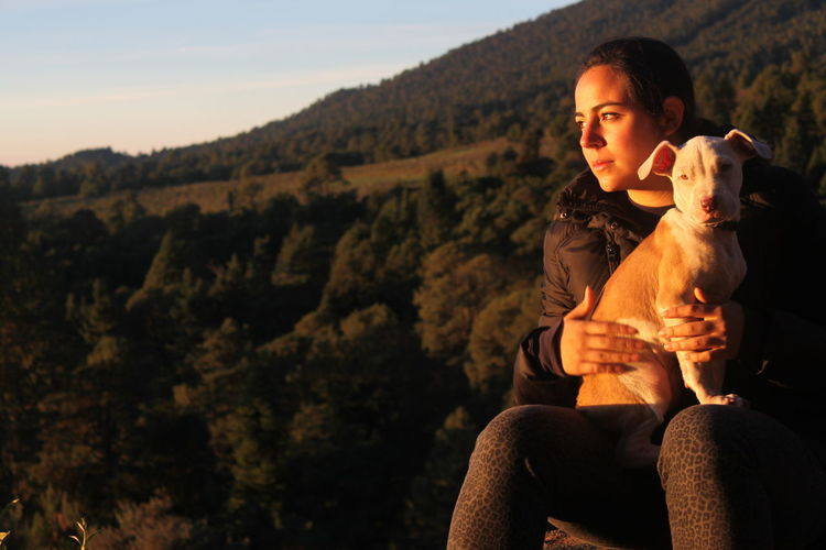 Young woman with dog sitting on mountain