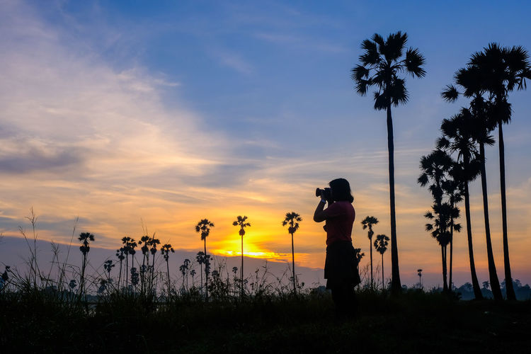 Silhouette man standing by palm tree against sky during sunset
