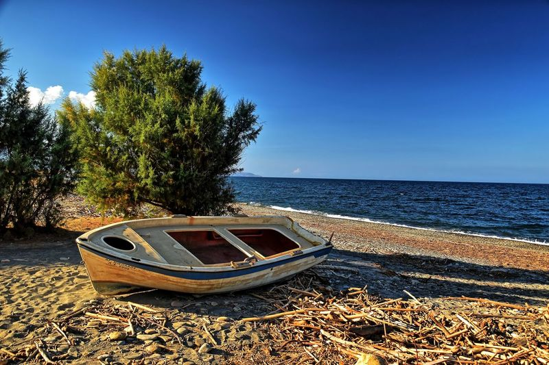 Boat moored on beach against clear sky
