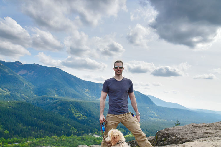 Portrait of man with dog standing against mountains