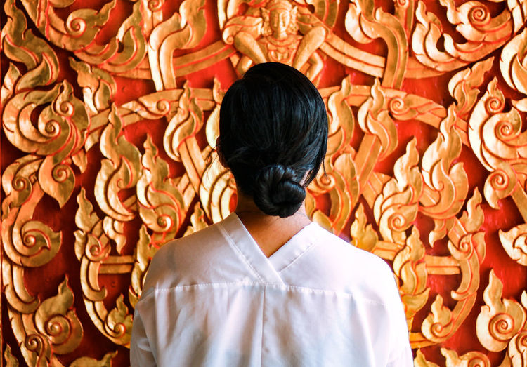 Rear view of young woman with hair bun standing against wall