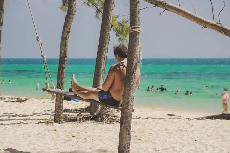 Man Sitting On Swing At Beach