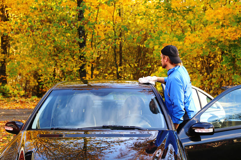 Full length of man standing by car during autumn