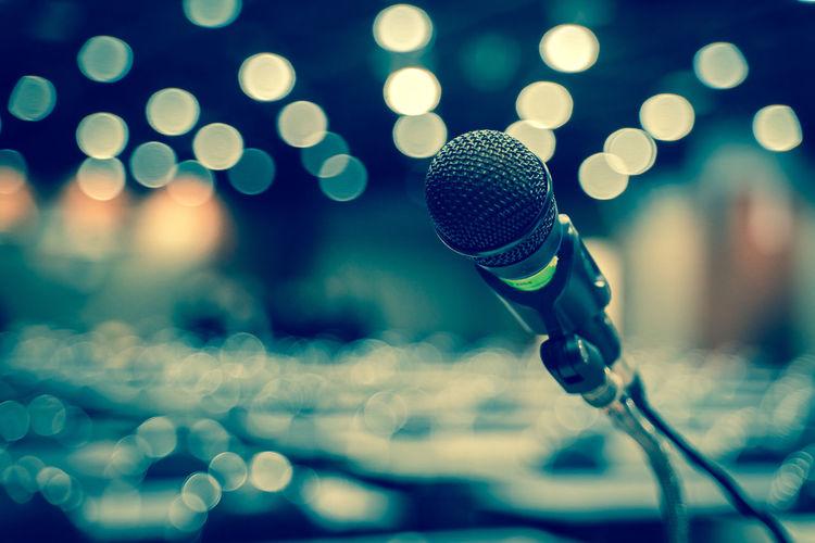 Close-up of microphone against illuminated lighting equipment