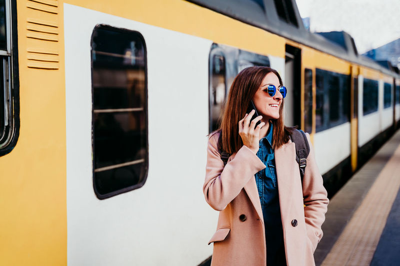 Young woman using smart phone on train