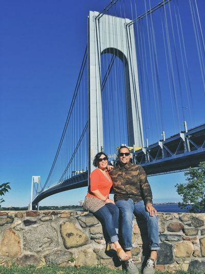 Low Angle View Of Mid Adult Couple Sitting On Retaining Wall Against Suspension Bridge