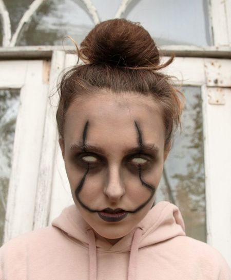 Close-up of blind girl with halloween make-up against building