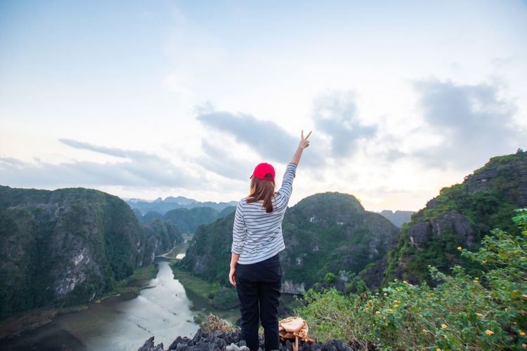 travel at Trang An, Ninh Binh, Vietnam One Person Real People Mountain Sky Leisure Activity Scenics - Nature Lifestyles Rear View Casual Clothing Standing Beauty In Nature Women Cloud - Sky Human Arm Day Mountain Range Adult Tranquil Scene Nature Freedom Arms Raised Outdoors Looking At View