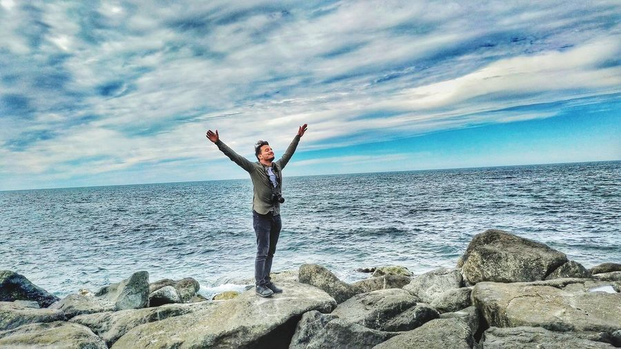 Man with arms raised standing on rocks at beach against sky