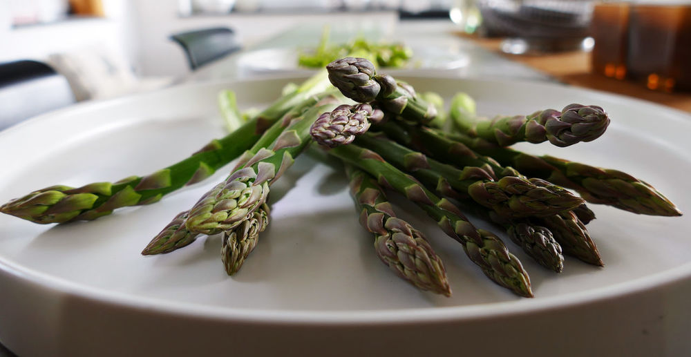 Close-up of asparagus in plate on table