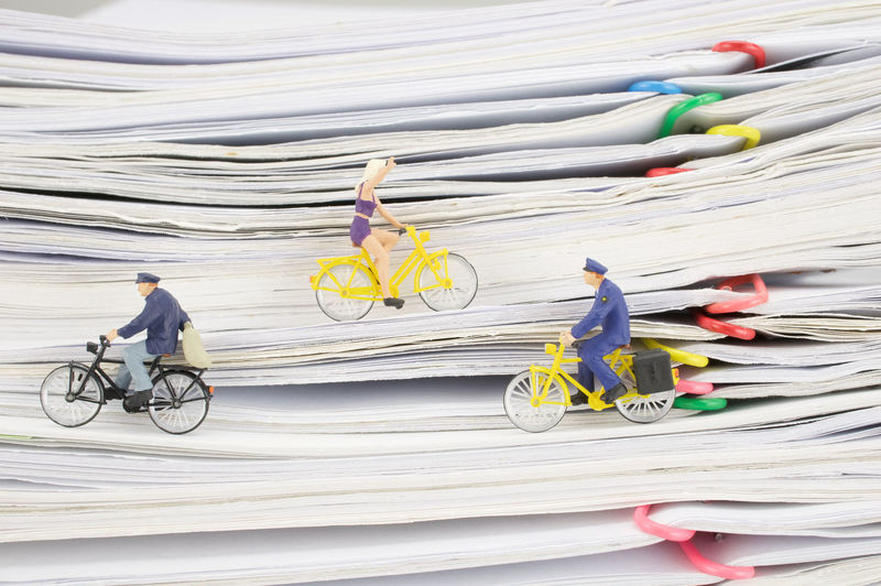 Close-up of figurines riding bicycles on stacked files