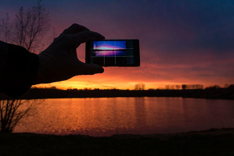 Man photographing sunset over lake through smart phone