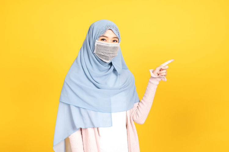 Portrait of person standing against yellow background