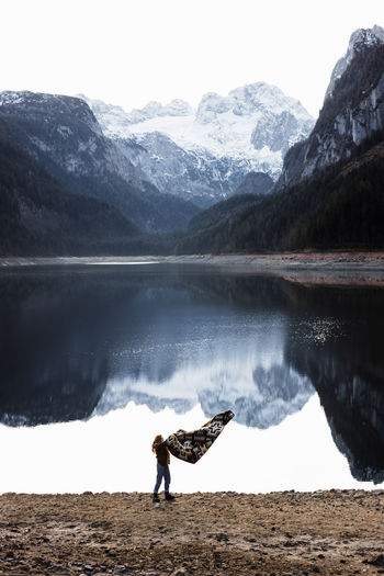 Full length of person on lake by snowcapped mountains against sky