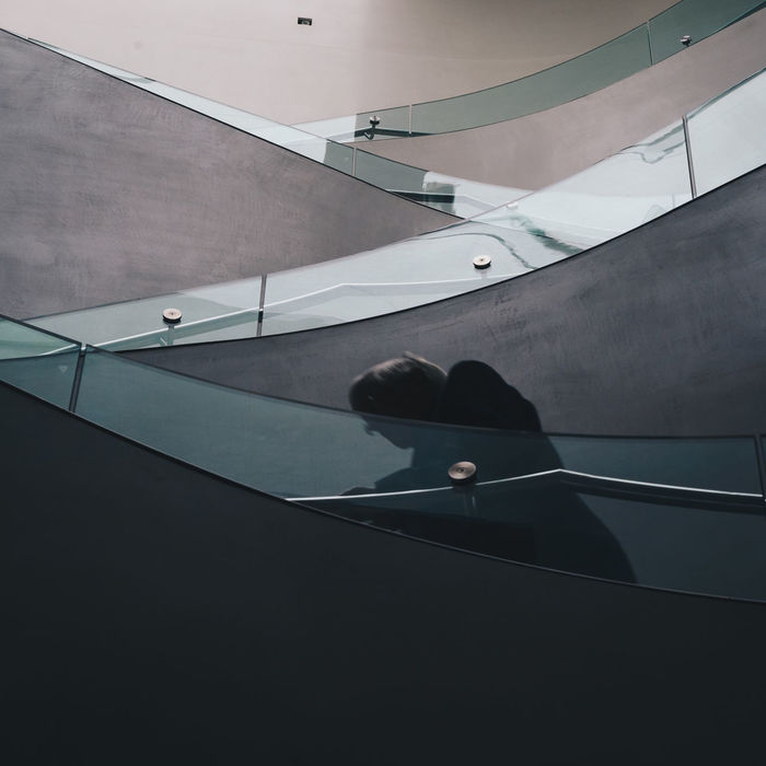 LOW SECTION OF WOMAN SITTING ON STEPS IN STAIRCASE