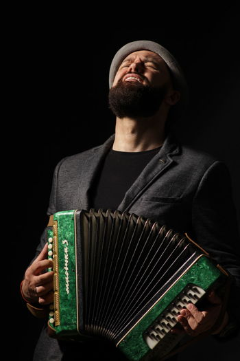 Portrait of young man playing on accordeon.