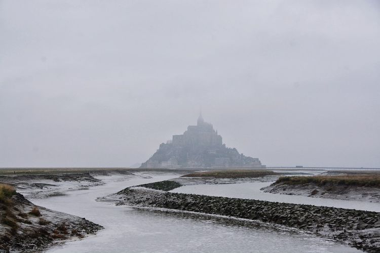 Stream flowing by mont saint-michel against sky during foggy weather