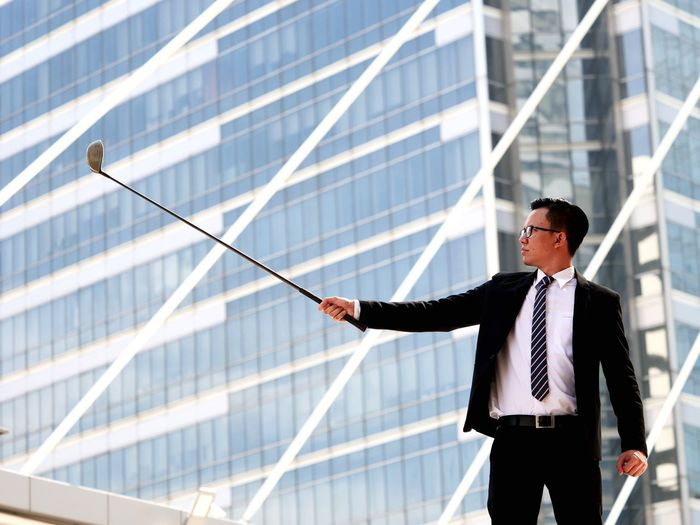 Businessman Holding Golf Club While Standing Against Building In City