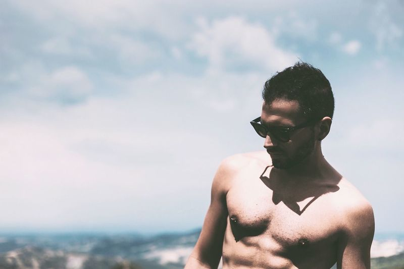 Shirtless Young Man Standing Against Sky