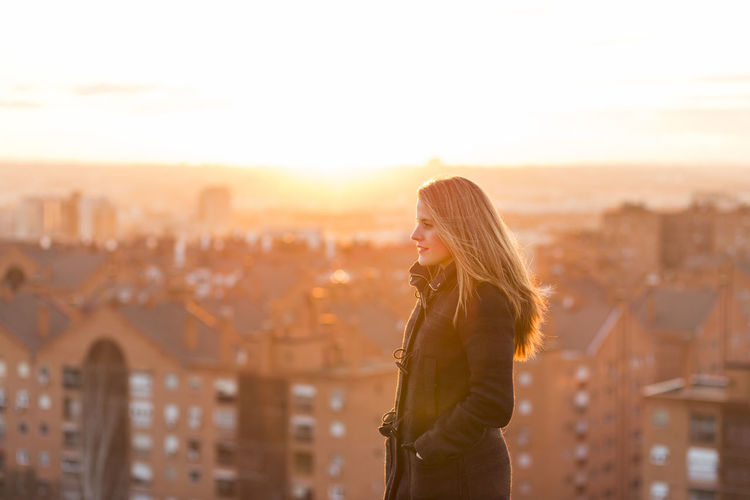 Young woman looking away against cityscape and sky