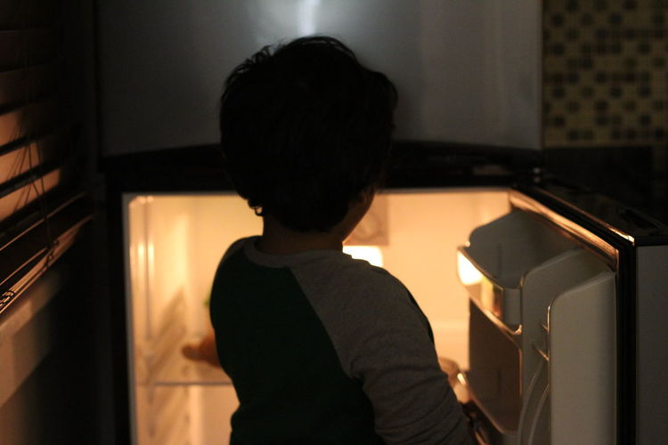 Boy standing by refrigerator at home