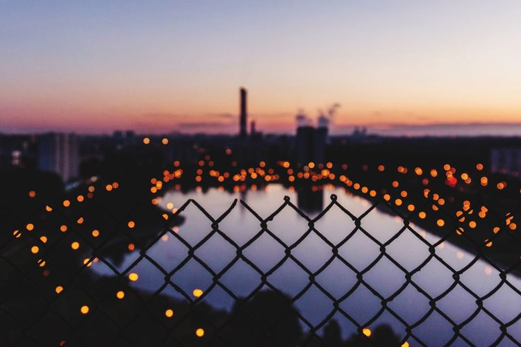 Fence by illuminated city against sky during sunset