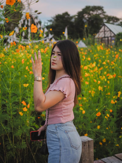 Side view of a beautiful young woman standing by plants