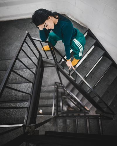 High angle view of man looking up at staircase