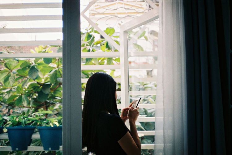 Woman using mobile phone at window