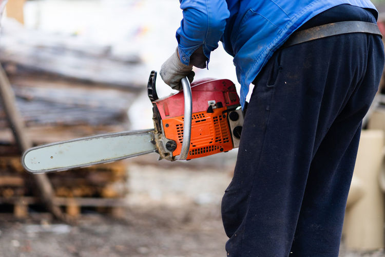 Midsection of man holding chainsaw
