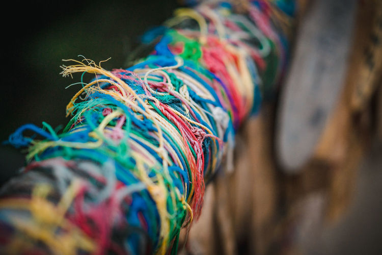 Close-up of multi colored threads tied on railing