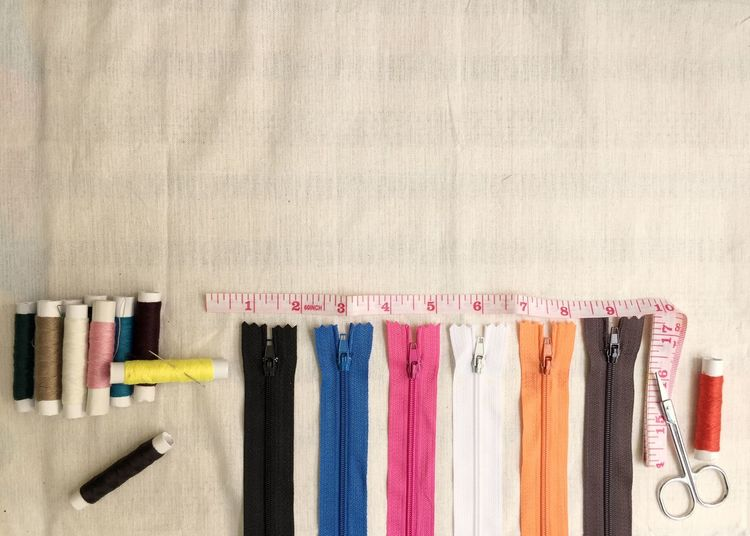 Close-up of multi colored zipper and spools on table