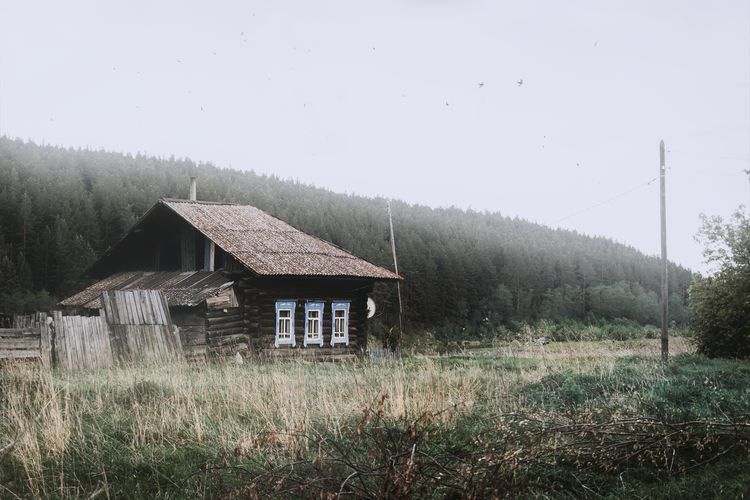 Abandoned house on field against sky