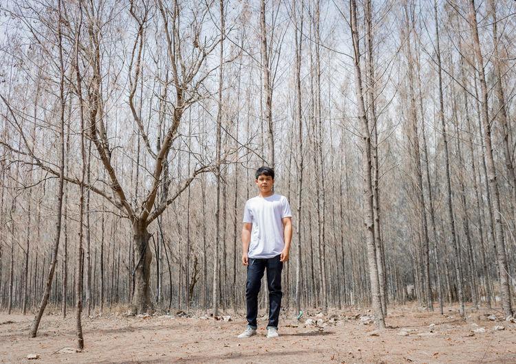 Full length portrait of man standing in forest