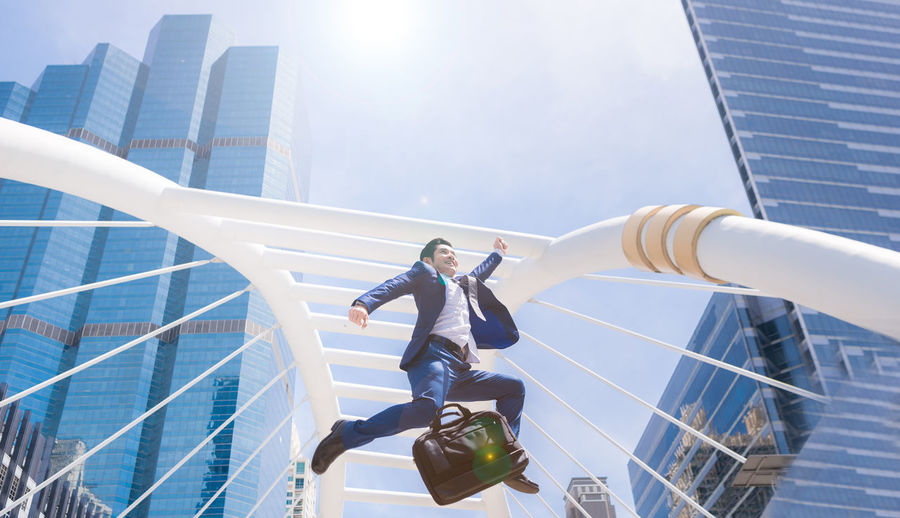 Low Angle View Of Businessman Jumping Against Buildings In City