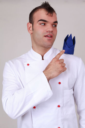 Handsome modern young male chef with a trendy hairstyle pointing to a creatively folded blue napkin balanced on his shoulder, isolated on grey Cooking Ornamental Uniform Bake Catering Decorative Fingers Folded Front View Hairstyle Holding Jacket Lifestyles Linen Looking At Camera Men Napkin One Person Portrait Real People Restaurant Standing Studio Shot Young Adult Young Men